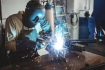 Welder welding metal in workshop — Stock Photo
