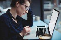 Junge Frau arbeitet am Laptop am Tisch im Café — Stockfoto