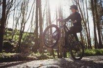 Горный велосипедист прыгает во время езды по грунтовой дороге в лесу — стоковое фото
