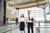 Pilote et agent de bord marchant à l'aéroport — Photo de stock