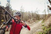 Фронтальний вид з гори байкер перевозять велосипеді по грунтовій дорозі — стокове фото
