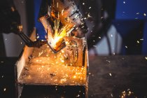 Cropped image of welder welding metal in workshop — Stock Photo