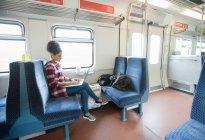 Volle Länge der Frau mit Laptop, während sie im Zug sitzt — Stockfoto