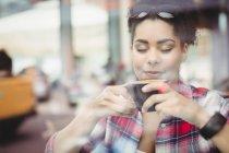 Gros plan de jeune femme avec les yeux fermés tout en buvant le café au restaurant — Photo de stock