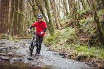 Вид спереди на байкера, идущего с велосипедом по течению в лесу — стоковое фото