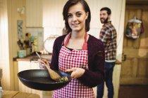 Женщина готовит еду на кухне дома с мужчиной на заднем плане — стоковое фото