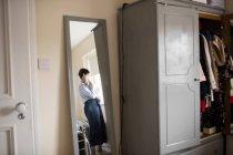 Reflexão no espelho da mãe segurando seu bebê adormecido em casa — Fotografia de Stock