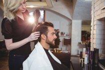 Homem arrumando seu cabelo secado com secador de cabelo no salão de beleza — Fotografia de Stock