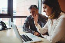 Mujer discutiendo con colega sobre portátil en la oficina - foto de stock