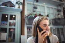 Девушка-флористка разговаривает по мобильному телефону в цветочном магазине — стоковое фото
