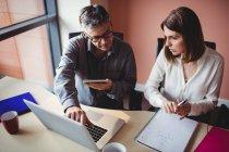 Mann und Frau diskutieren im Büro über digitales Tablet und Laptop — Stockfoto