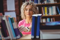 Donna che rimuove il libro dalla libreria in biblioteca — Foto stock