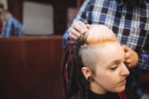 Woman getting her hair trimmed with trimmer in barber shop — Stock Photo