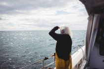 Вид сбоку на Фишмана, стоящего на лодке и смотрящего в море — стоковое фото