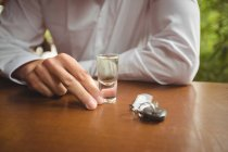 Середині розділі чоловік тримає скляні Текіла вистрілив в барна стійка в барі — стокове фото