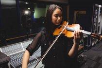 Studentessa che suona il violino in uno studio — Foto stock