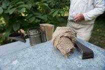 Gros plan du fumeur d'abeilles et de l'équipement dans le jardin du rucher — Photo de stock