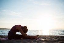 Вид сбоку на женщину, занимающуюся йогой на пляже в солнечный день — стоковое фото
