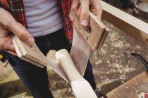 Средняя секция человека, работающего на деревянной доске на верфи — стоковое фото