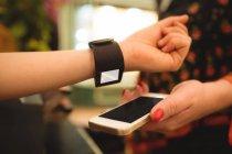 Закри жіночих рук оплаті через smartwatch — стокове фото