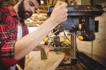 Mann bohrt Loch auf Holzplanke in Bootswerft — Stockfoto
