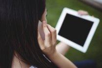 Primer plano de la mujer que habla en el teléfono móvil mientras usa la tableta digital - foto de stock