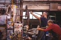 Souffleurs de verre façonnant un verre sur la pipe à souffler à l'usine de soufflage de verre — Photo de stock