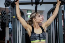 Woman performing stretching exercise with pull up bar in gym — Stock Photo