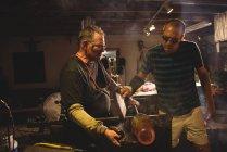 Team di soffiatori di vetro che modellano vetro fuso presso la fabbrica di soffiaggio del vetro — Foto stock