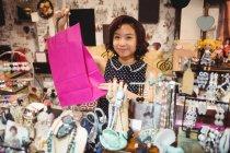 Mulher sorridente segurando um saco de compras rosa na loja de antiguidades — Fotografia de Stock