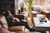 Висока кут зору вагітна жінка розслаблюючим у вітальні на дому — стокове фото