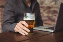 Человек держит стакан пива и использует ноутбук в баре — стоковое фото