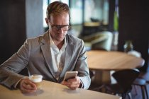 Businessman using mobile phone while having coffee at cafe — Stock Photo