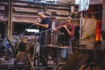 Glassblowers shaping a glass on blowpipes at glassblowing factory — Stock Photo
