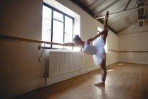Молодая балерина практикует балетные танцы в баре в студии — стоковое фото