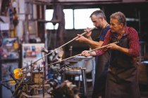 Glassblowers shaping a glass on the blowpipes at glassblowing factory — Stock Photo