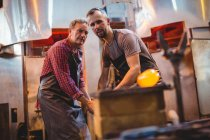 Glassblowers shaping a molten glass at glassblowing factory — Stock Photo