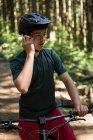 Ciclista masculina falando no celular em floresta na luz solar — Fotografia de Stock