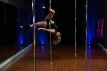 Вид збоку полюс танцюрист практикуючих полюс танці в студії — стокове фото
