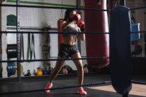 Boxeuse pratiquant la boxe avec sac de boxe dans un studio de fitness — Photo de stock