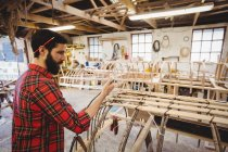 Man preparing wooden boat frame in boatyard — Stock Photo