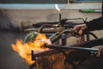 Cropped image of Glassblower giving final touch to piece of glass with glassblowing torch at glassblowing factory — Stock Photo