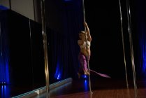 Female Pole dancer practicing pole dance in studio — Stock Photo