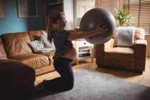 Вид сбоку на беременную женщину, занимающуюся фитнесом в гостиной дома — стоковое фото