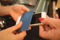 Kunde gibt am Abrechnungsschalter Telefon und Kreditkarte an Kassierer ab — Stockfoto