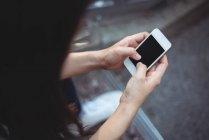 Frau schreibt SMS auf Handy im Café — Stockfoto