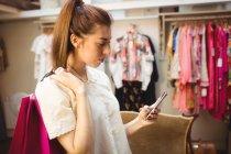 Mulher usando telefone celular enquanto faz compras na loja boutique — Fotografia de Stock