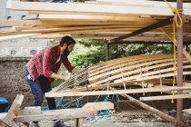 Mann bereitet Holzbootrahmen in Bootswerft vor — Stockfoto