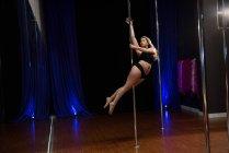 Apasionada bailarina polaca practicando pole dance en estudio - foto de stock