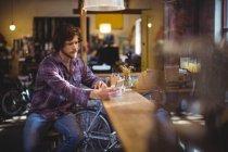 Механік за допомогою мобільного телефону на лічильник в майстерні — стокове фото